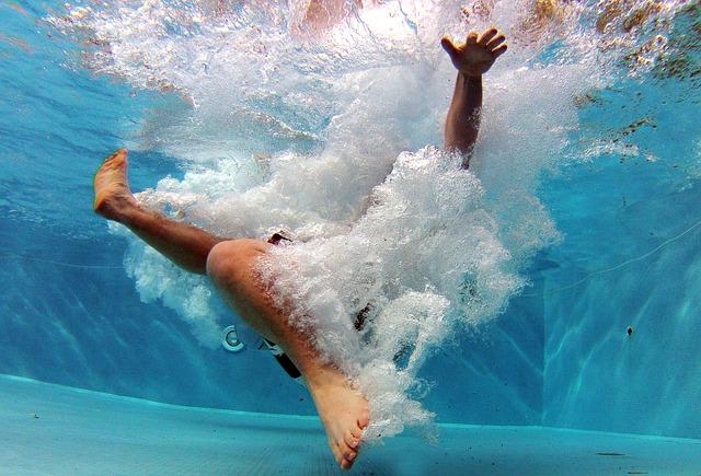 Záběr na plavce ze dna bazénu